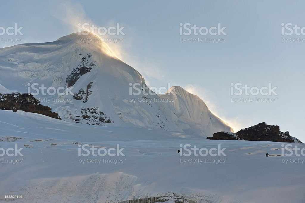 Mountaineers climbing dawn mountain peak Himalayas stock photo