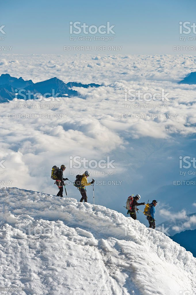 Mountaineers climbing down snowy ridge above clouds Alps stock photo