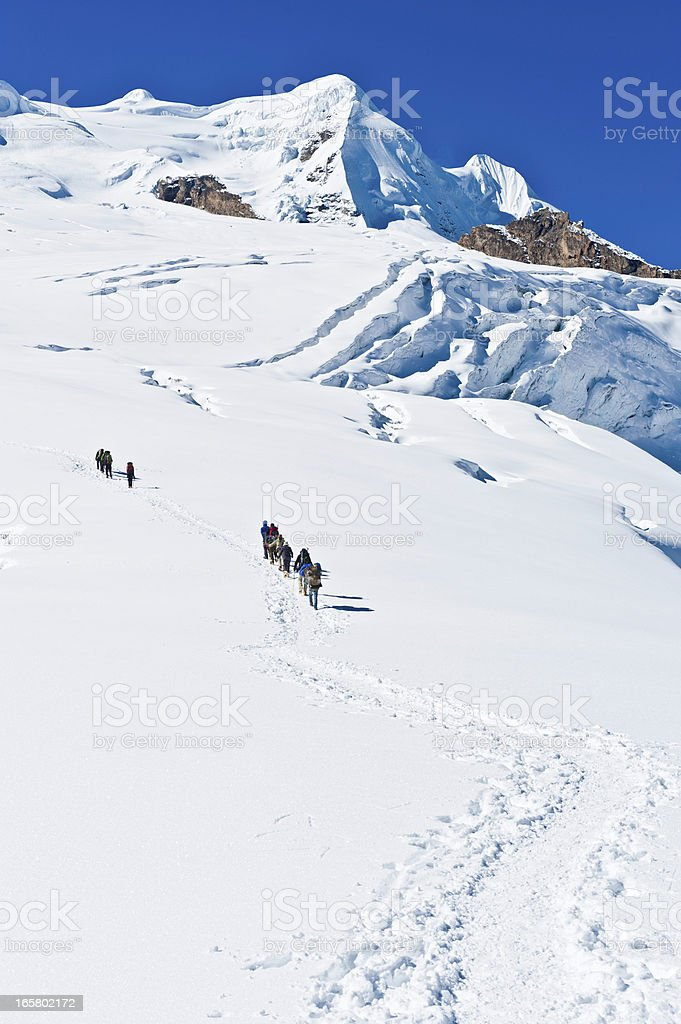 Mountaineers climbing snow capped peaks Himalayas Nepal stock photo