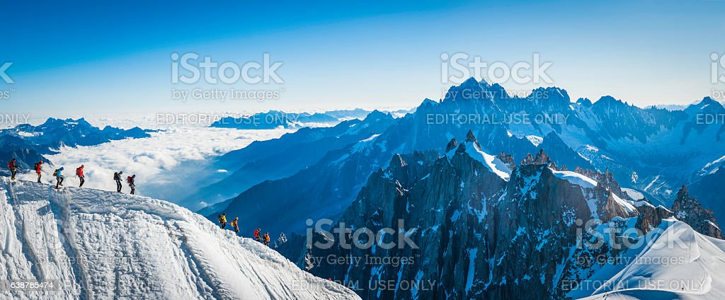 Mountaineers climbing snowy ridge high above clouds Alps panorama France stock photo