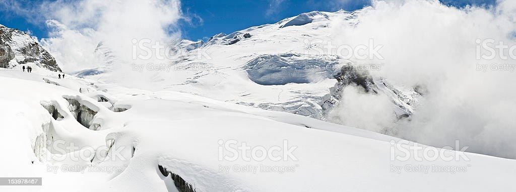 Mountaineers crossing crevasses snow white glacier pass winter Himalayas Nepal royalty-free stock photo