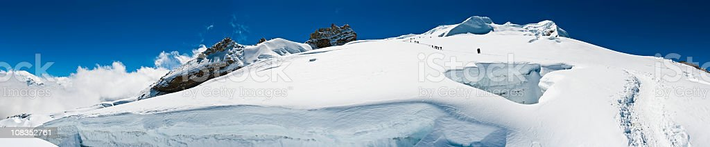 Mountaineers crossing high altitude glacier crevasses snow mountain peaks Himalayas stock photo