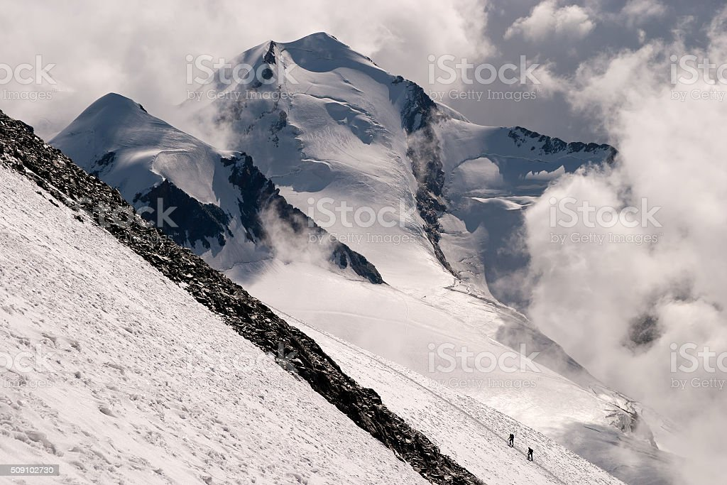 Mountaineers in the distance climbing a steep slope stock photo