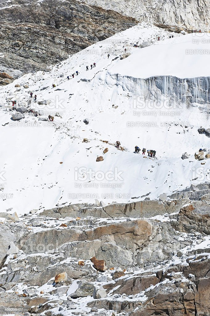 Mountaineers Sherpas and porters climbing glacier Himalayas Nepal stock photo