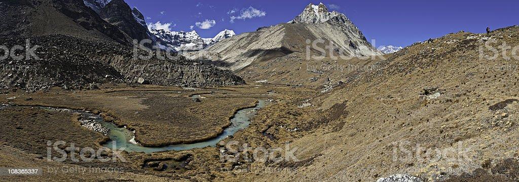 Mountaineers trekking through high mountain wilderness Himalayas Nepal panorama stock photo
