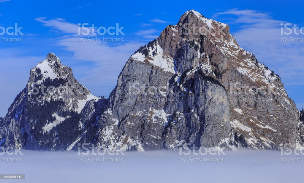 Mountains Kleiner Mythen and Grosser Mythen rising from sea of fog stock photo