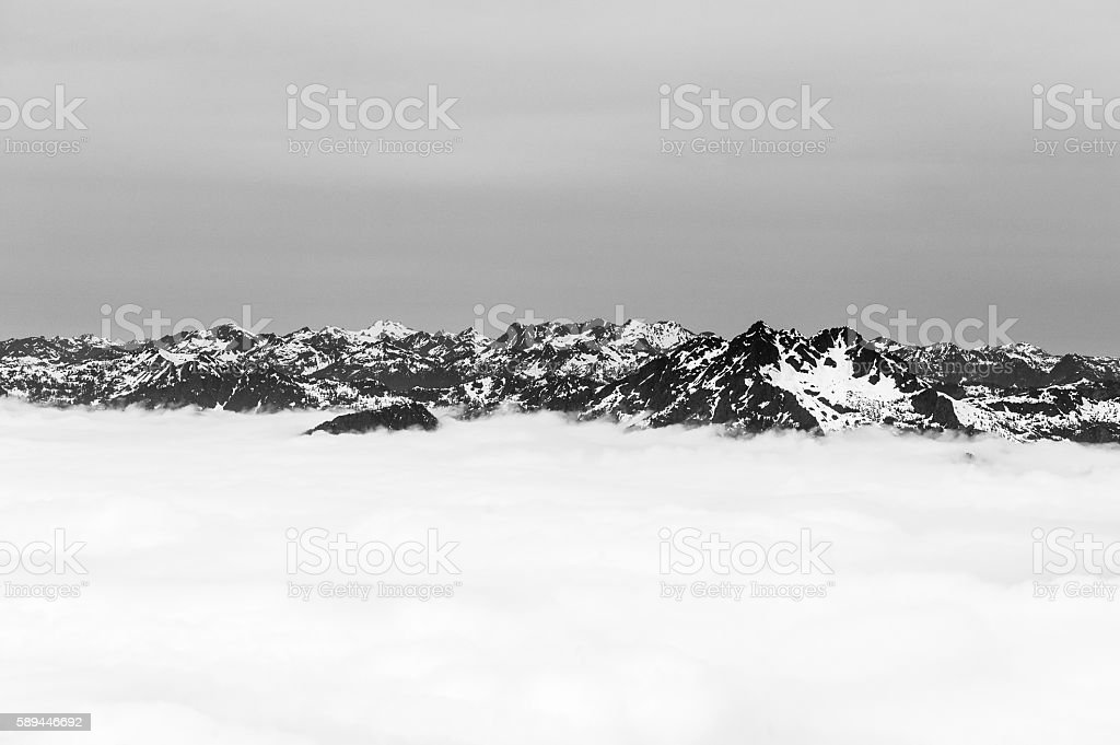 Mountains shrouded by clouds in black and white stock photo