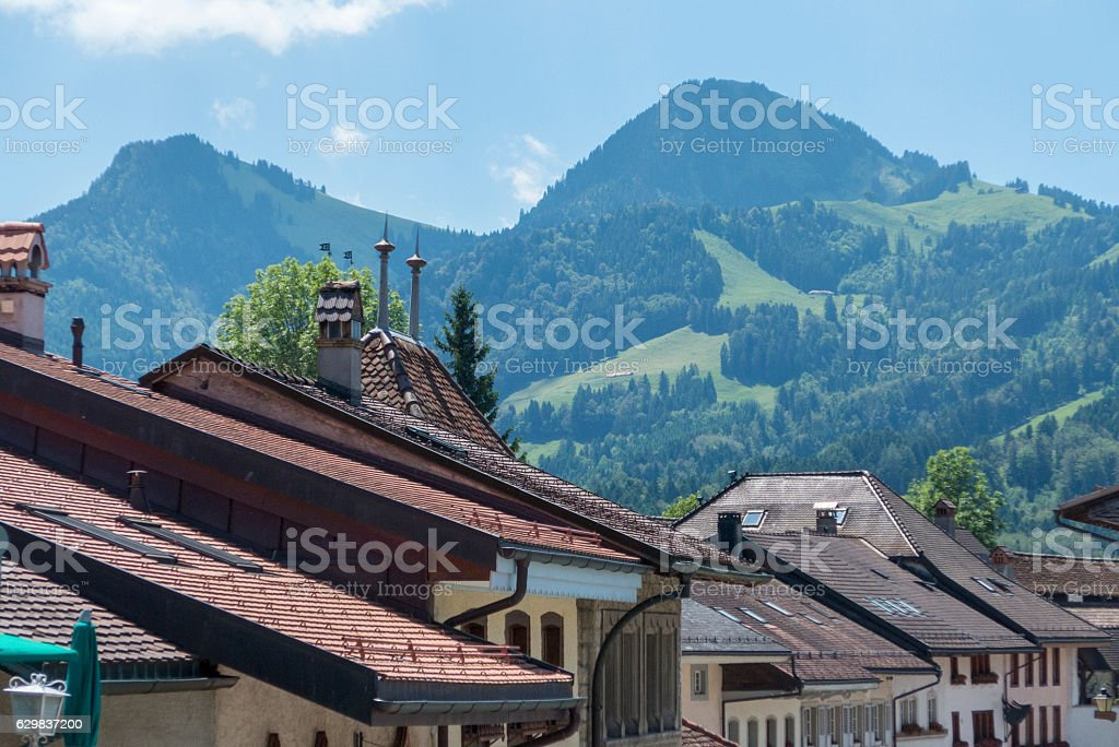 Mountains viewed over rooftops of Gruyères, switzerland stock photo