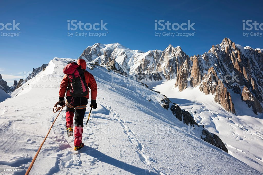 Mountaneer climbs a snowy ridge in Mont Blanc stock photo