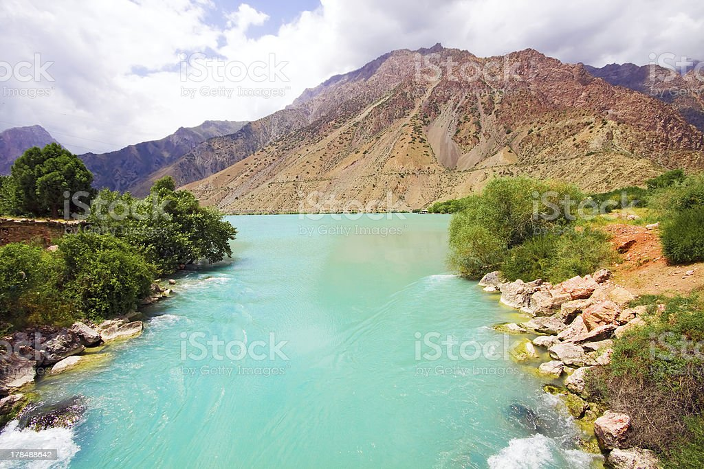 Mountanious moraine river and trees under cloudy sky royalty-free stock photo