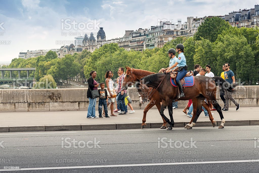 Mounted police riding past the bystanders on bridge in Paris stock photo