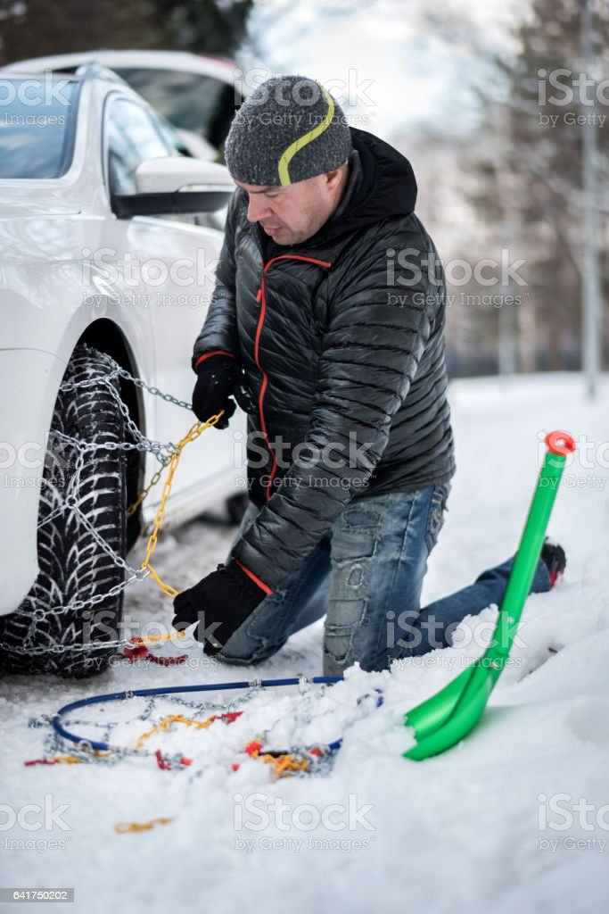 Mounting snow chains on a car tire stock photo