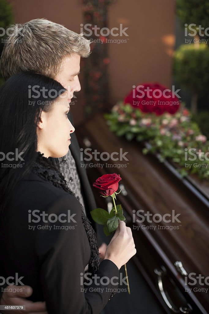 Mourning Couple at Funeral with coffin stock photo