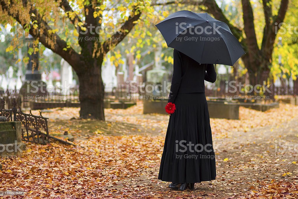 Mourning woman with umbrella wearing black in cemetery in fall stock photo