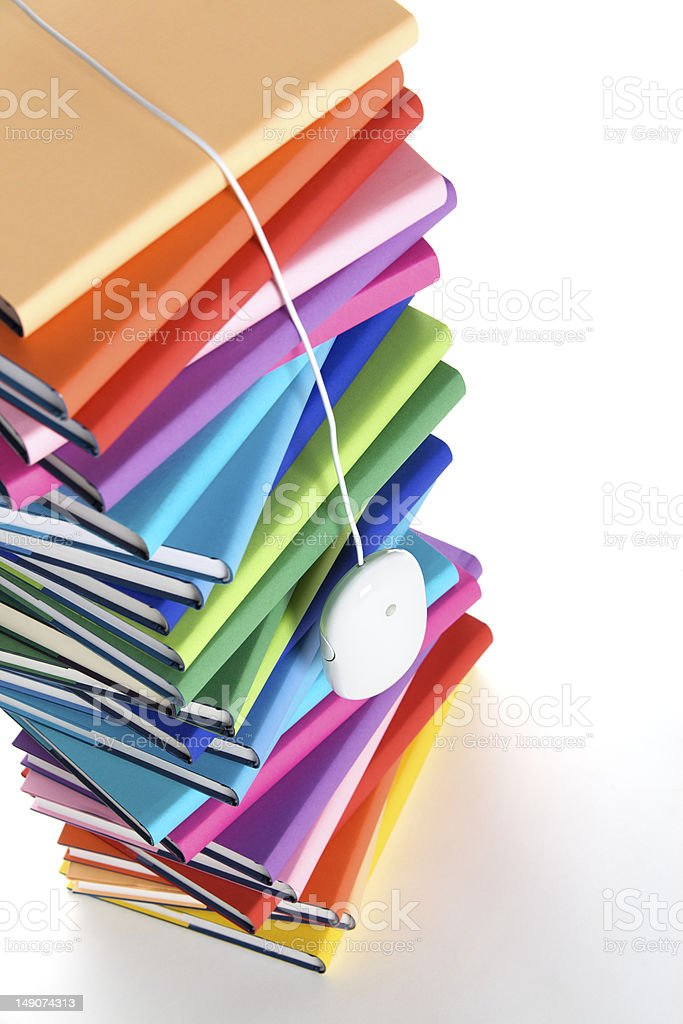 Mouse hanging from top of multi-colored book stack royalty-free stock photo