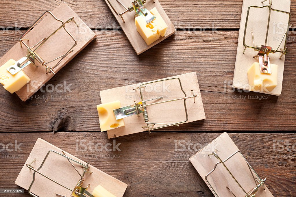 Mouse traps with cheese on old wooden table stock photo