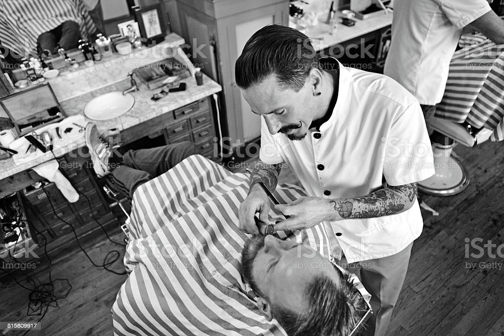 moustached barber shaving customers beard stock photo