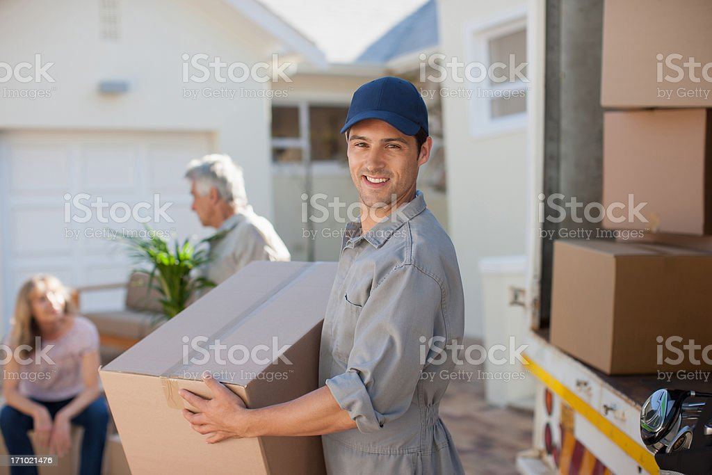 Mover helping couple move into new home stock photo