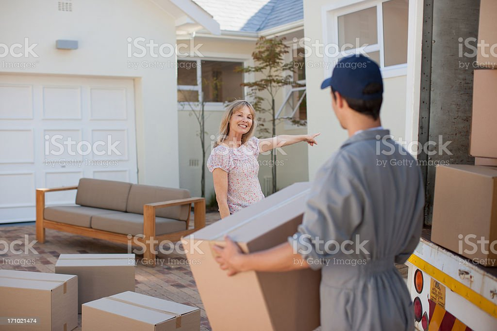 Mover helping woman move into new home royalty-free stock photo