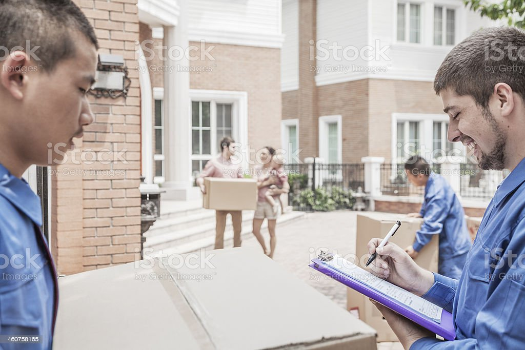 Mover holding clipboard and invoice, family in the background stock photo