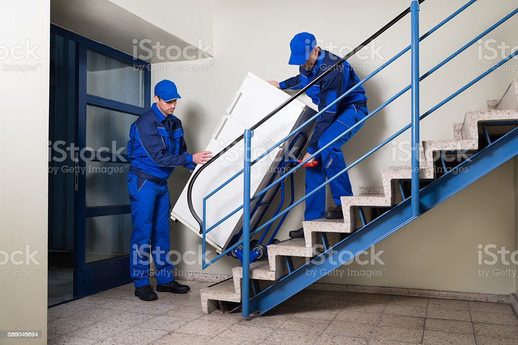 Movers Carrying Refrigerator While Climbing Steps stock photo