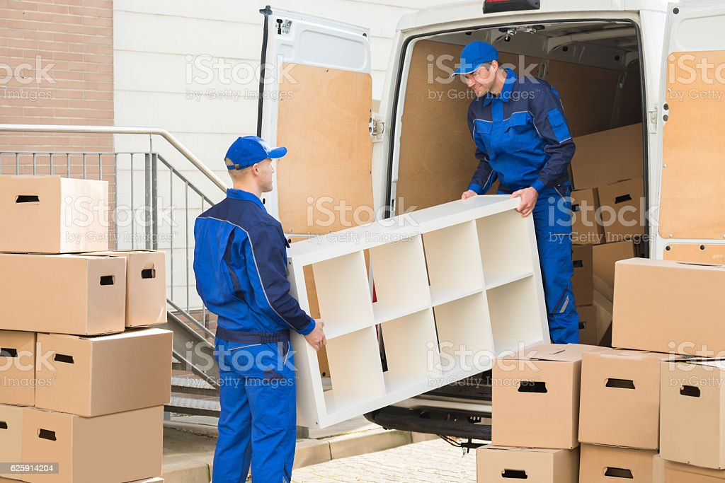 Young male movers unloading furniture and cardboard boxes from truck...