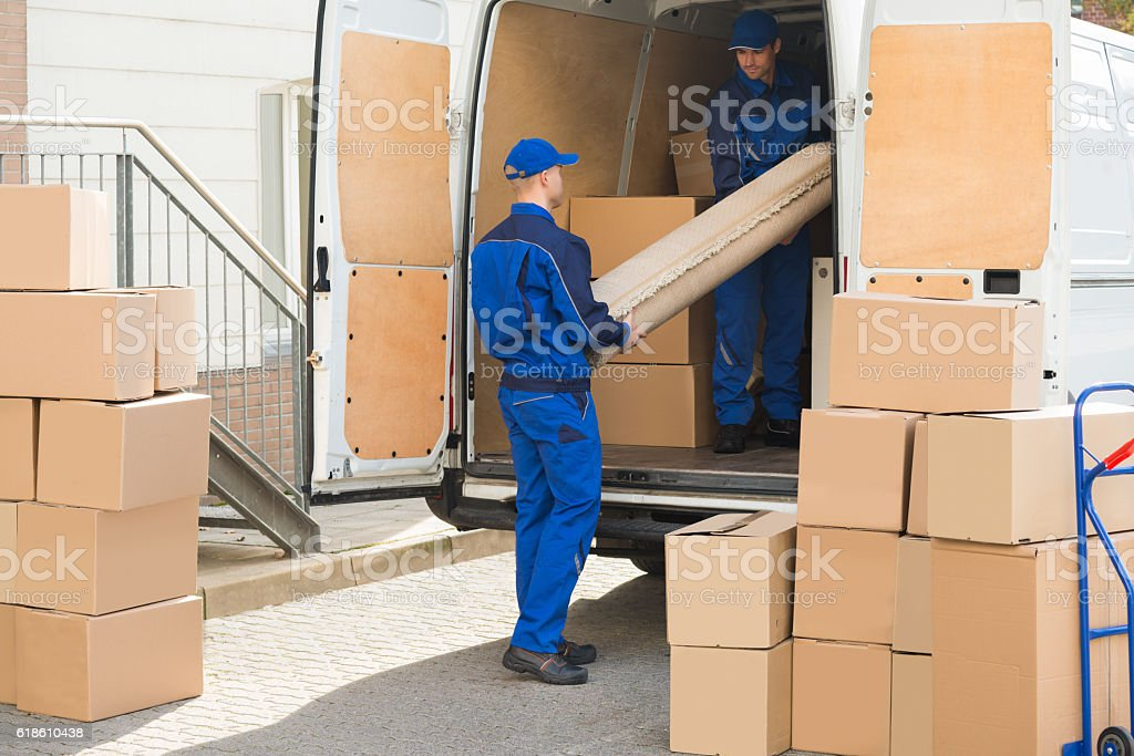 Movers Unloading Rolled Up Rug From Truck stock photo