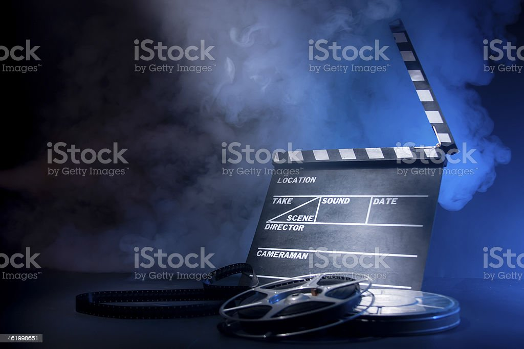 Movie clapper and film reels stock photo