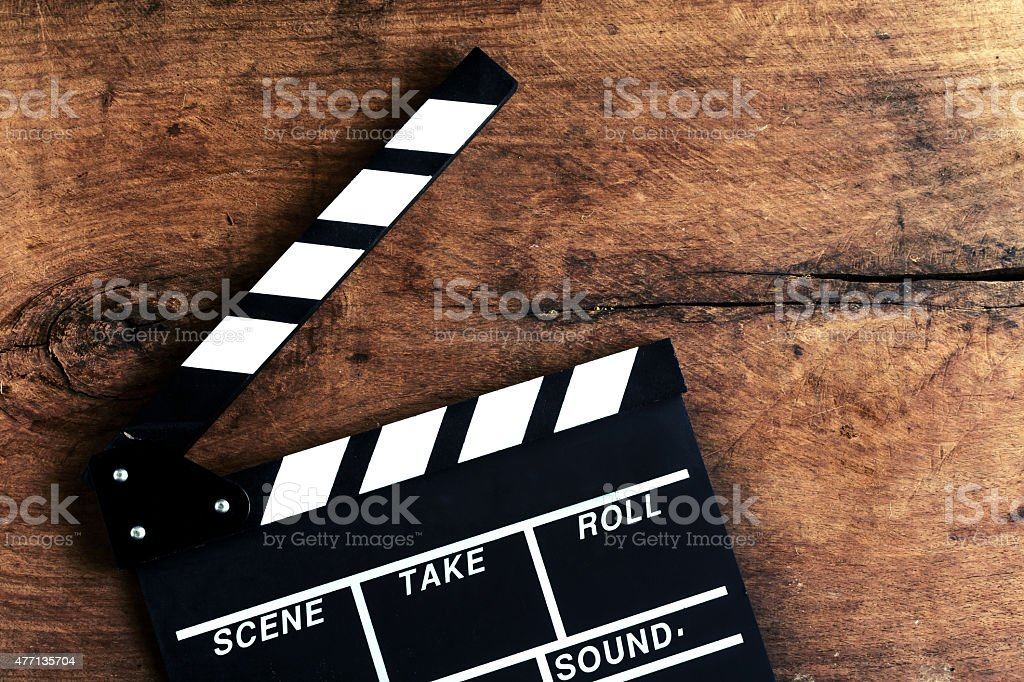 Movie clapper on old wooden background stock photo