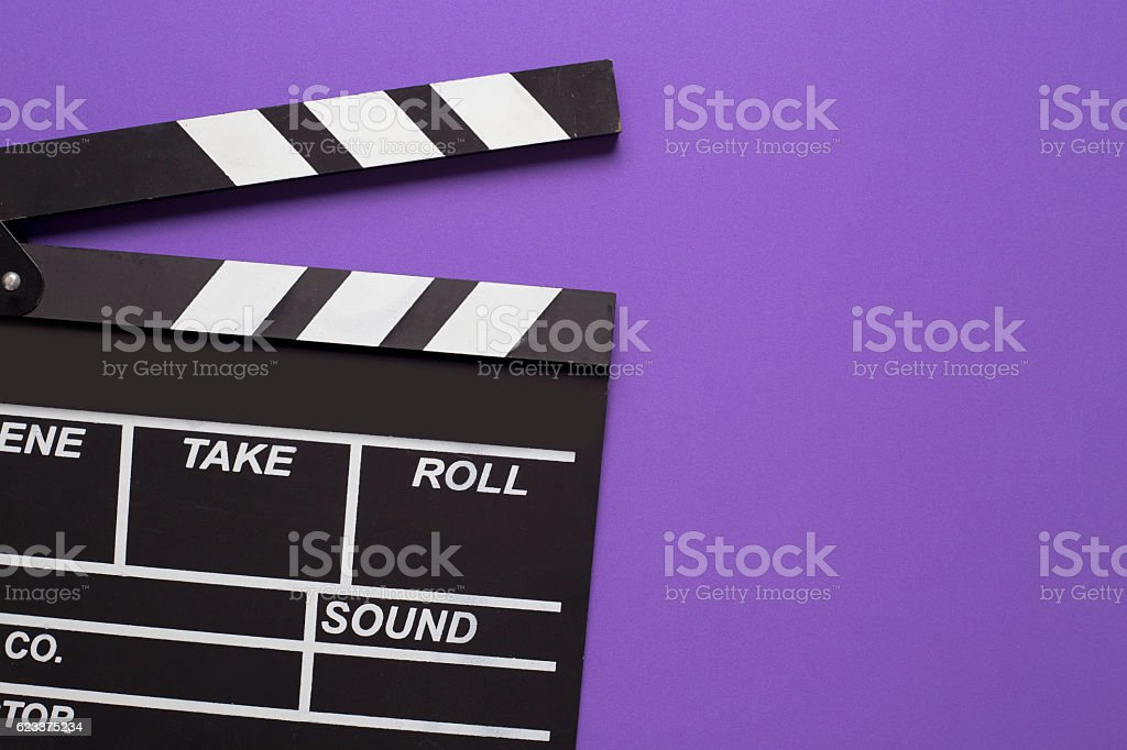 movie clapper on violet background stock photo