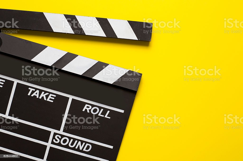 movie clapper on yellow background stock photo