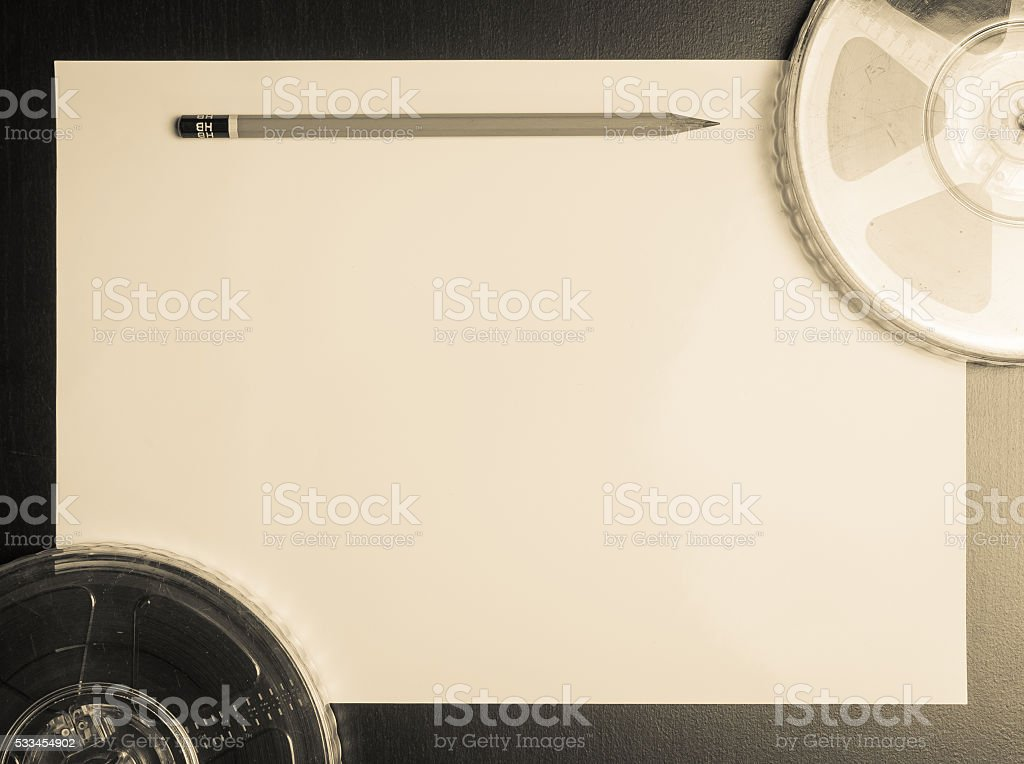 Movie film roll with pencil on paper vintage background stock photo