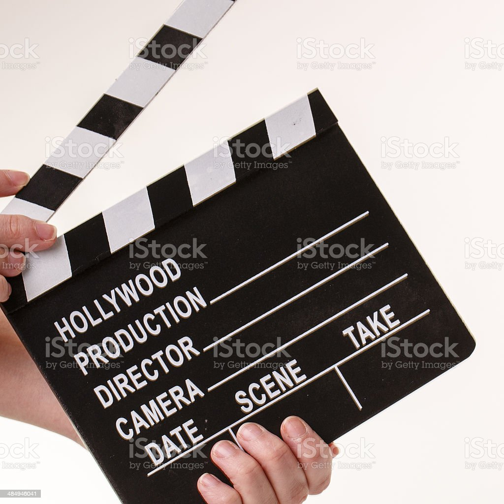 Movie flapper in woman?s hands on white background stock photo