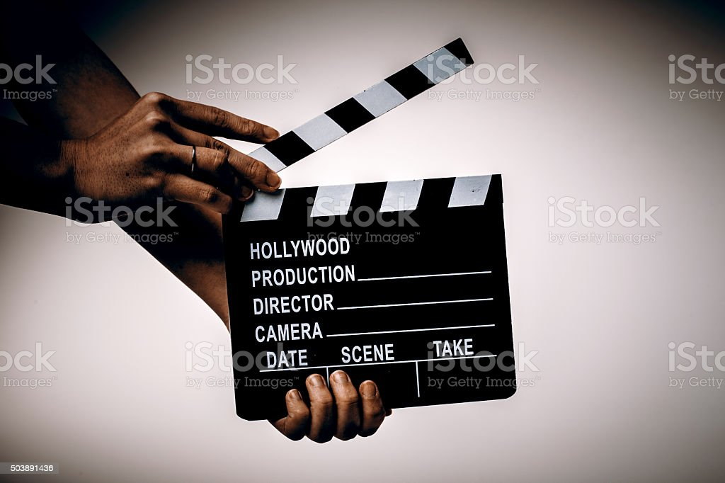 Movie flapper in womans hands on white background stock photo