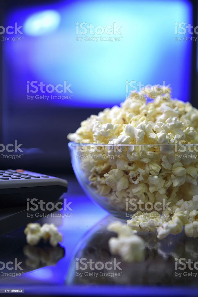 Movie night. Bowl with popcorn and remote control. stock photo