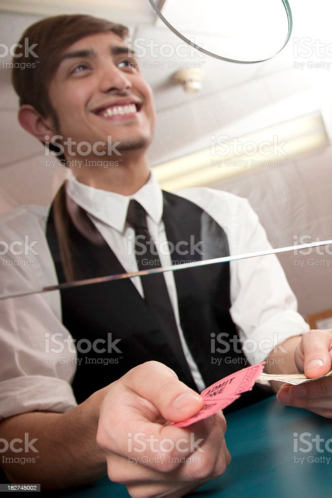 Movie Ticket Attendant in Booth Collecting Money for Tickets stock photo