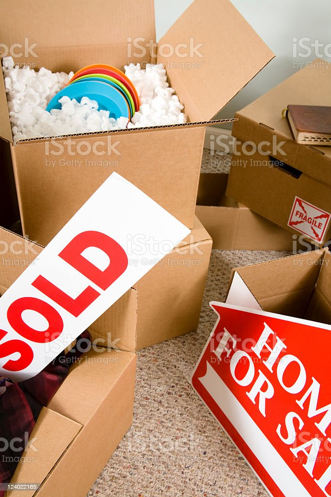 Moving boxes, home. Packing, unpacking. Sold, home for sale signs. royalty-free stock photo