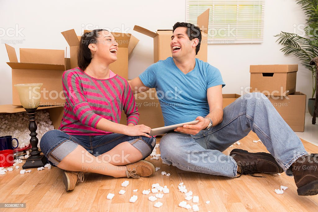 Moving Boxes: Latin couple laugh, use digital tablet. Relocation concept. stock photo