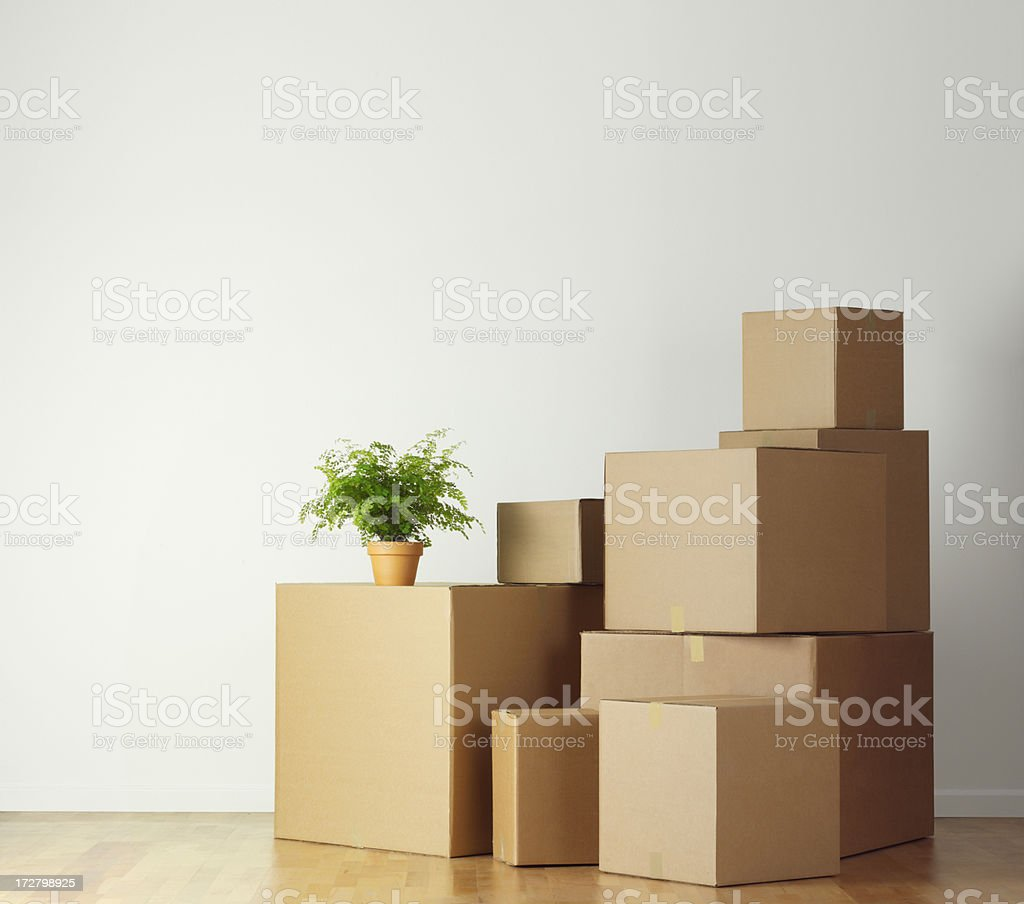 Moving boxes stacked in an empty room ready for movers stock photo