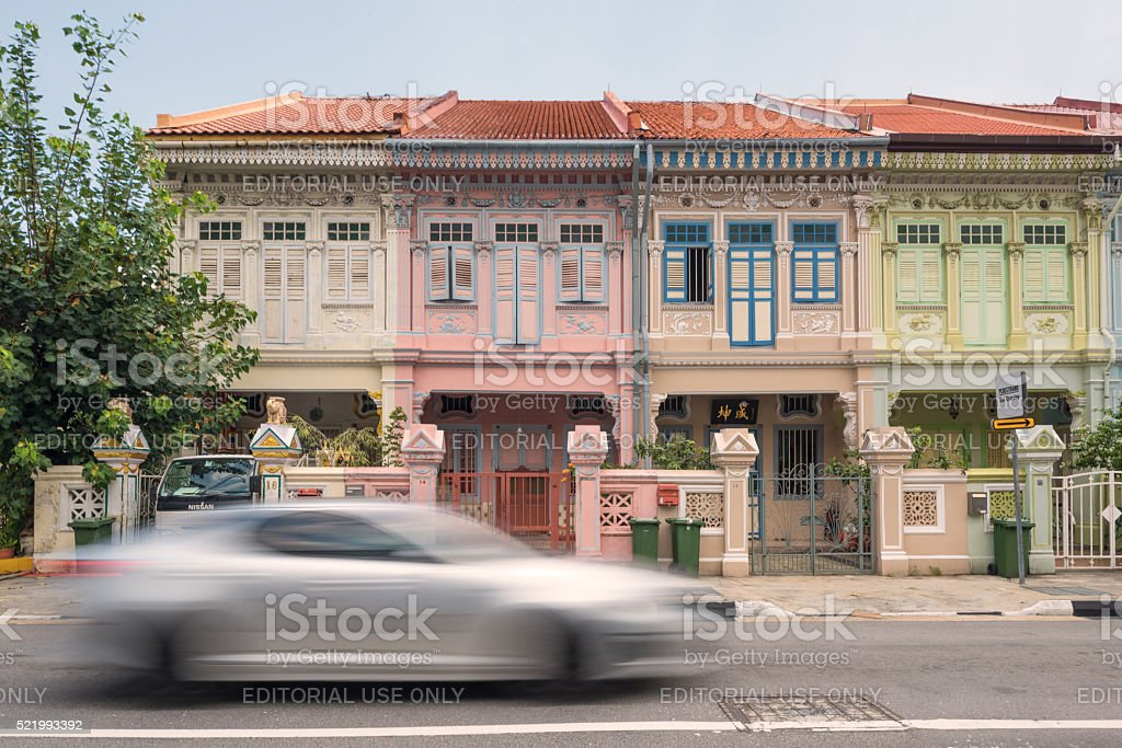 Moving car in front of conservation shophouses stock photo