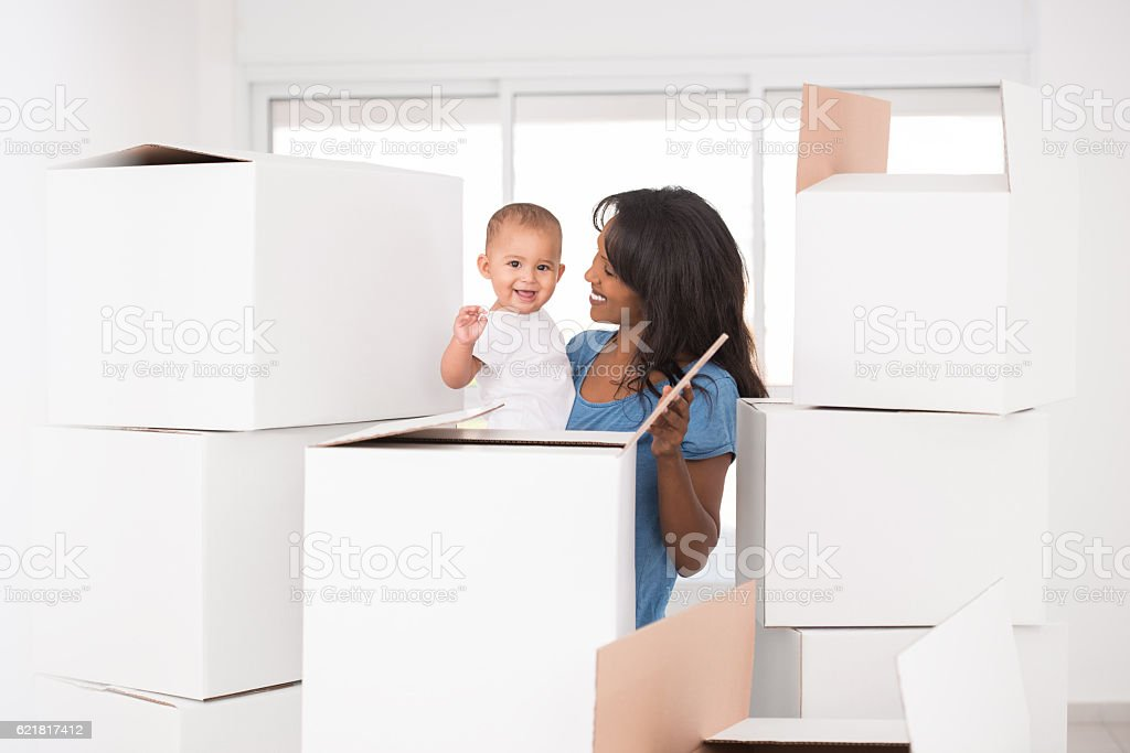 Moving day. Mother and baby unpacking. stock photo
