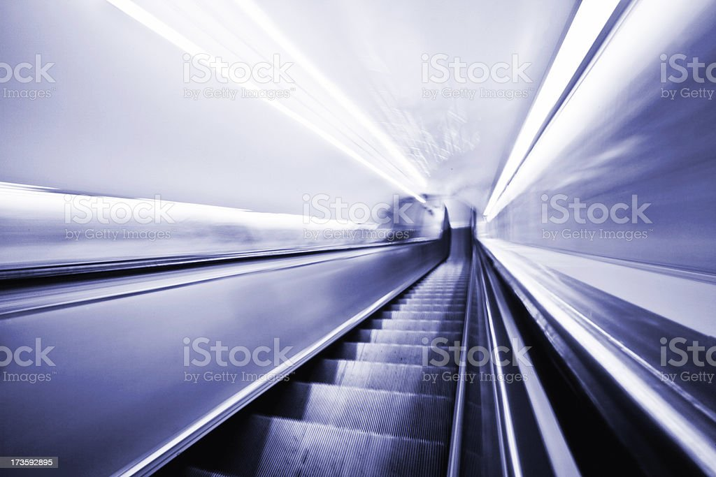 Moving Escalator-Motion Blurred in Blue-More blurs below royalty-free stock photo
