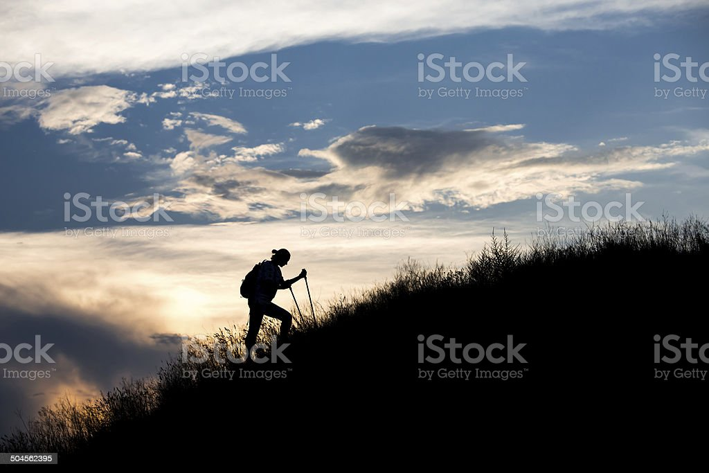 Moving hiker in front of sunset stock photo