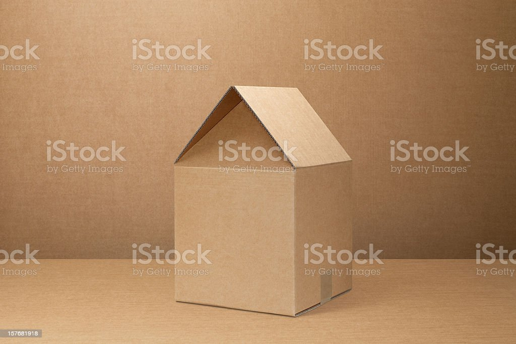 Moving home. Cardboard box shaped house. stock photo