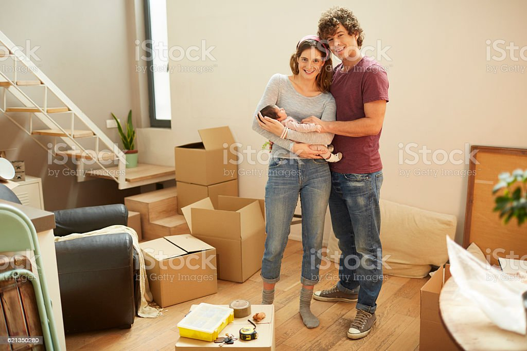 Moving home new beginnings.  Couple portrait with baby. stock photo