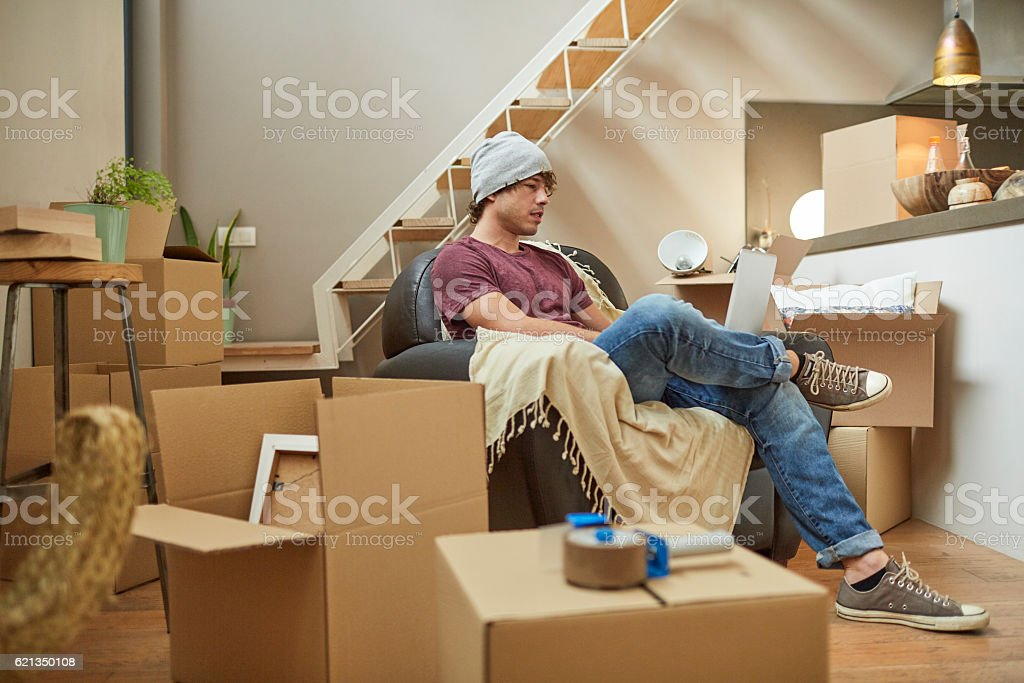 Moving home new beginnings. Relaxing with laptop. stock photo