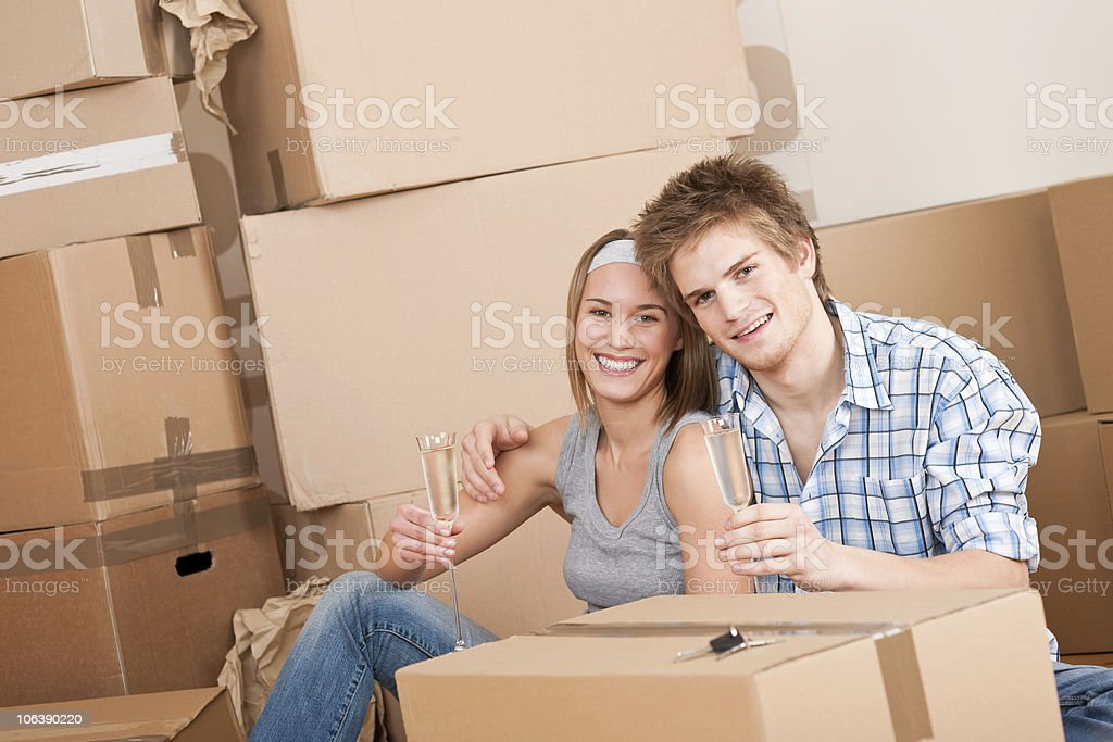 Moving house: Happy man and woman celebrating royalty-free stock photo