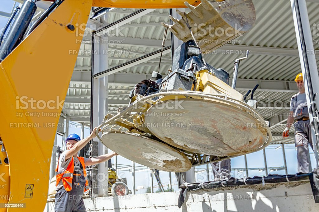 Moving power trowel machine with excavator on new job site. stock photo