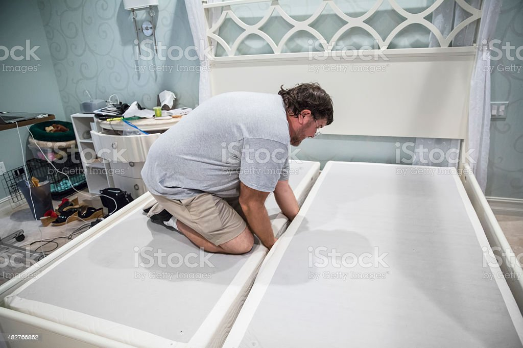 Moving series: Caucasian man disassembles adjustable bed to move it stock photo