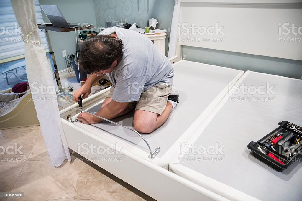 Moving series: Caucasian man takes apart adjustable bed to move stock photo